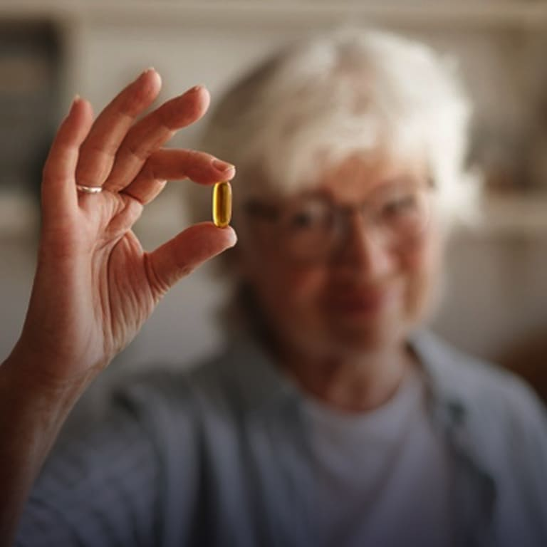 Uma pessoa idosa segurando uma cápsula