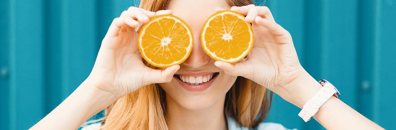Mulher segurando 2 fatias de laranja