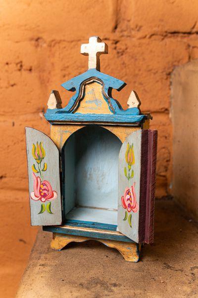 Mini oratório em madeira com portas escuras detalhe dourado